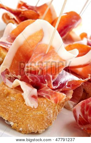 closeup of a plate with some typical spanish pinchos de jamon, serrano ham served on bread