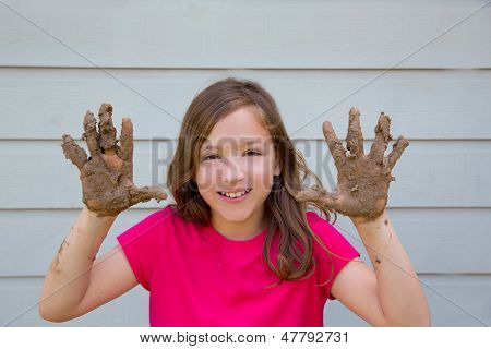 happy kid girl playing with mud with dirty hands smiling portrait