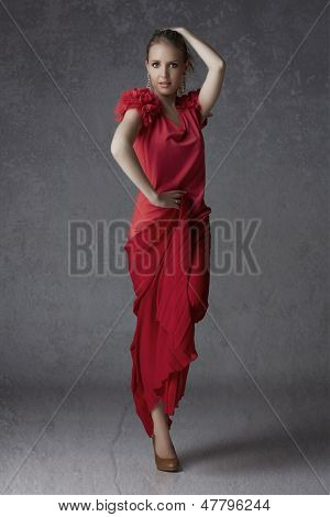Beautiful blond woman in red pleated skirt and ruffled top balancing on one foot on grunge studio background - full length