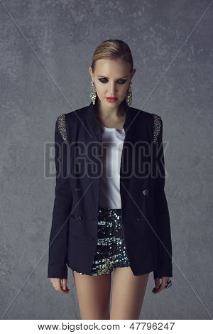 beautiful young blond woman with messy hair in a black blazer and sequin green shorts on grunge studio background