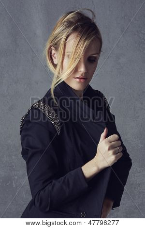 beautiful young blond woman with messy hair in a black blazer on grunge studio background