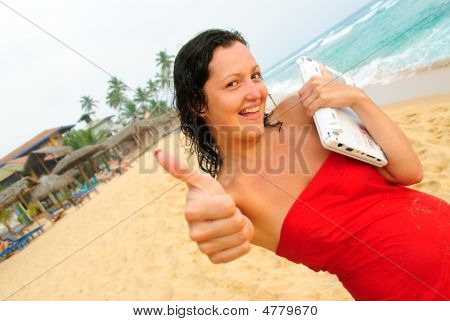 Smiling Young Woman Giving Thumbs Up With Laptop On Beach