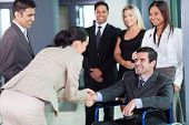stock photo of handicapped  - young businesswoman greeting handicapped business partner and team - JPG