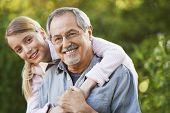 stock photo of granddaughter  - Portrait of young girl embracing grandfather from behind in backyard - JPG
