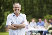 image of family bonding  - Portrait of senior man with arms crossed and family having lunch in background - JPG