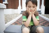 stock photo of boredom  - Sad little boy with hands on chin sitting on front steps of house - JPG