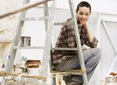 Portrait of young female painter sitting on ladder in work site