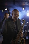 picture of saxophone player  - Saxophone player with man playing double bas in background on stage - JPG