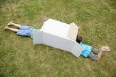 Elevated view of two boys playing in cardboard box in the backyard