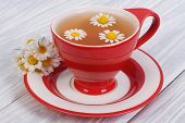 stock photo of chamomile  - herbal tea with chamomile flowers in a red cup - JPG