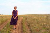 stock photo of oddities  - eccentric woman in the retro dress on the road - JPG
