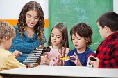 stock photo of daycare  - Beautiful preschool teacher teaching students to play xylophone in class - JPG