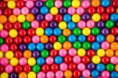 picture of gumballs  - Brightly colored gum balls laying flat background - JPG