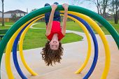 stock photo of playtime  - children kid girl upside down on a park playground ring game - JPG