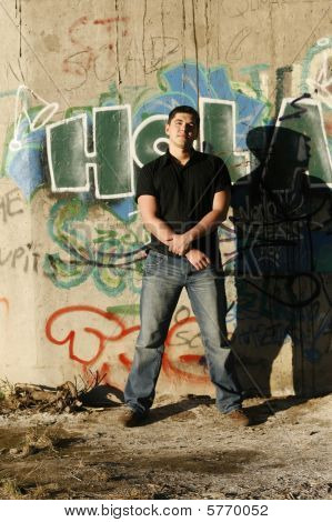 Young Handsome Man Standing By The Wall With Graffiti On It