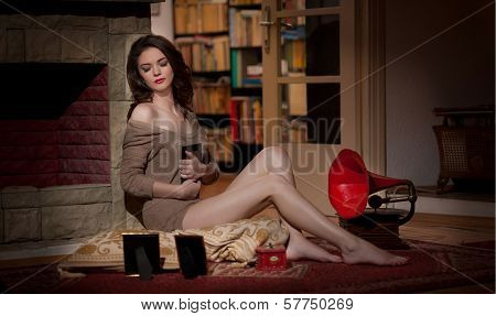 Beautiful sexy woman near a red gramophone surrounded by photo frames in vintage scenery. Portrait