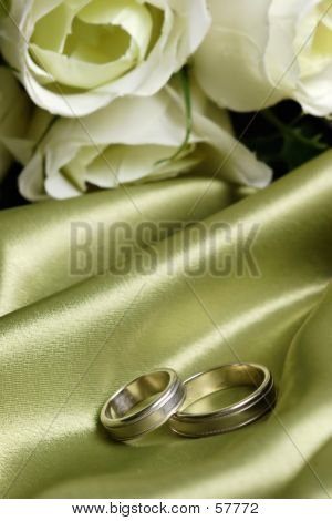 Pair Of Wedding Bands On Green Satin