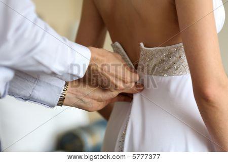 Groom Helping Birde To Put Wedding Dress On