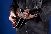 stock photo of bluegrass  - Hands playing a mandolin isolated on a blue background - JPG