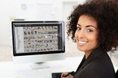 Smiling Businesswoman Editing Photographs