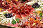 stock photo of cheese platter  - Table full of meat and cheese focus on prosciutto - JPG