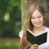 Young Teenage Girl Reading Book Near Tree
