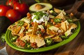 stock photo of jalapeno peppers  - Homemade Unhealthy Nachos with Cheese Sour Cream and Vegetables