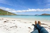 Man's Legs Relaxing On A Scottish White Beach