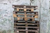 stock photo of wooden pallet  - Stack of old wooden pallets on the background of the old wall - JPG