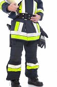 pic of lower body  - Body of a fireman showing his uniform with high visibility neon trim and his equipment including his safety helmet gloves belt and fire axe - JPG