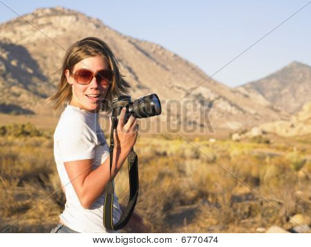 Young Woman Wearing Sunglasses Holding Camera