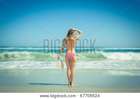 Gorgeous fit woman in striped bikini and sunhat at beach on a sunny day