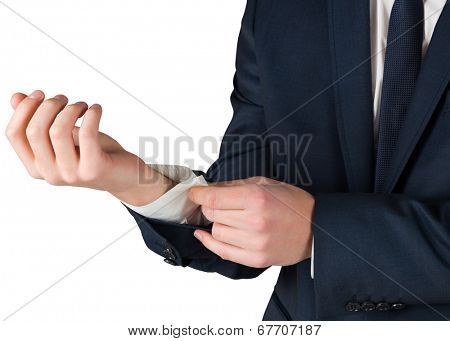 Businessman adjusting his cuffs on shirt on white background