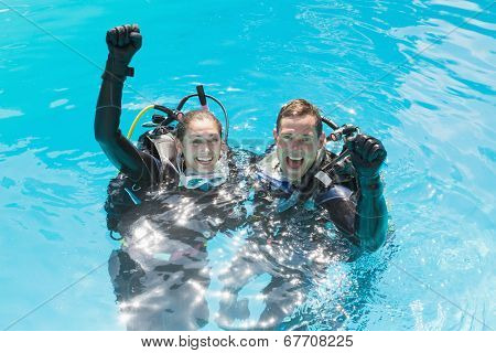 Smiling couple on scuba training in swimming pool looking at camera on a sunny day