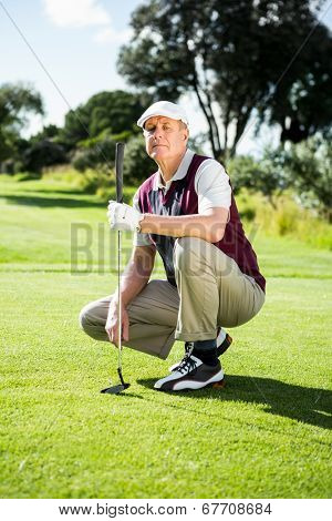 Golfer kneeling holding his golf club on a sunny day at the golf course