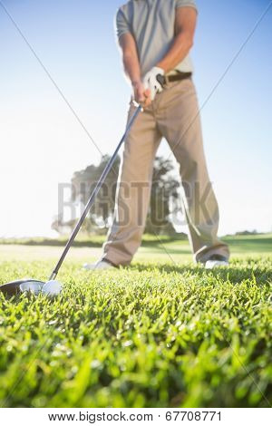 Golfer about to hit golf ball on a sunny day at the golf course