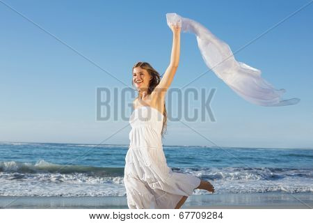 Beautiful blonde in white sundress on the beach with cocktail on a sunny day