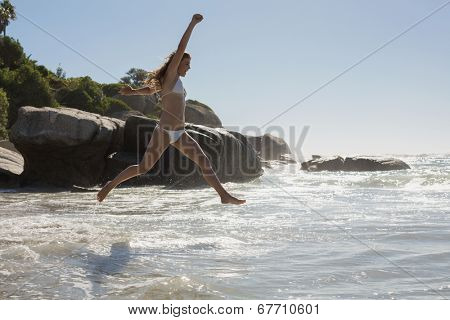 Beautiful smiling woman in white bikini leaping on the beach on a sunny day