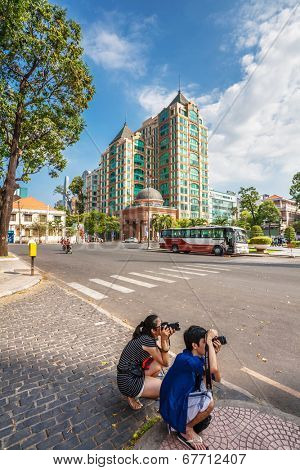 HO CHI MINH, VIETNAM - APRIL 28, 2014: Tourists take pictures on street in Ho Chi Minh City. Its formerly named Saigon, which was officially renamed to Ho Chi Minh City July 2, 1976