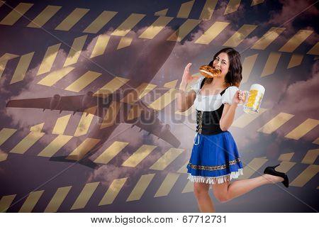 Pretty oktoberfest girl holding beer tankard and pretzel against cloudy sky