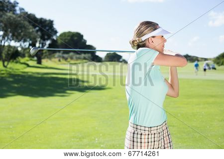 Lady golfer teeing off for the day on a sunny day at the golf course