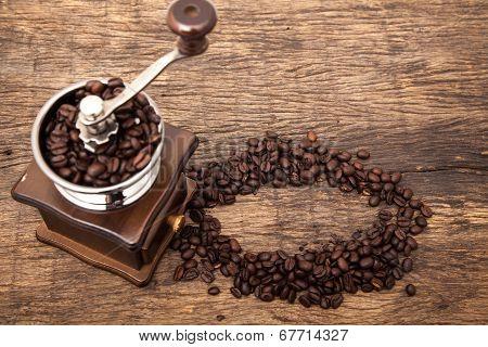 Vintage Coffee Bean Grinder Next To Circle Shape Coffee Beans