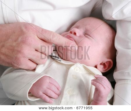 Adult Male Caressing Newborn Baby