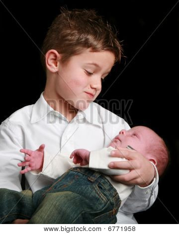 Young Boy And Baby Looking At Each Other