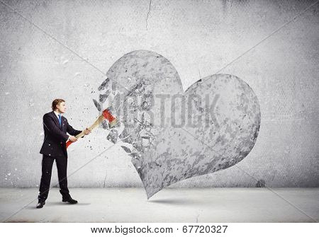Young businessman breaking stone heart with axe