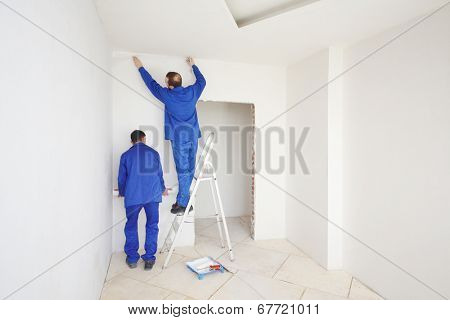 Two workers in blue clothes glue paint fiberglass on ladder in new apartment
