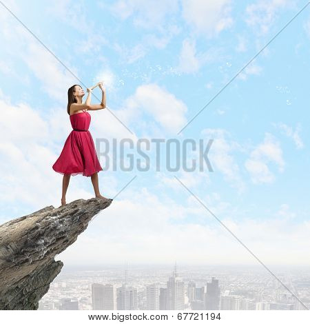 Young woman in red dress on edge of rock playing fife
