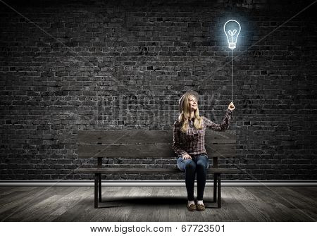 Young woman in casual holding bulb balloon