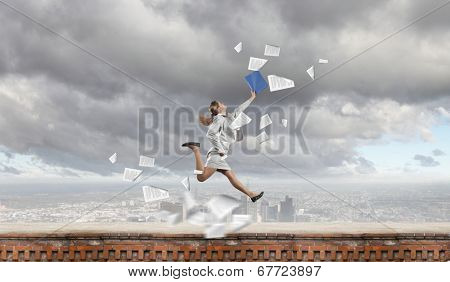 Young happy businesswoman with folder in hand jumping cheerfully