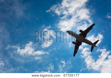 Dark silhouette of an airplane flying over the blue skies